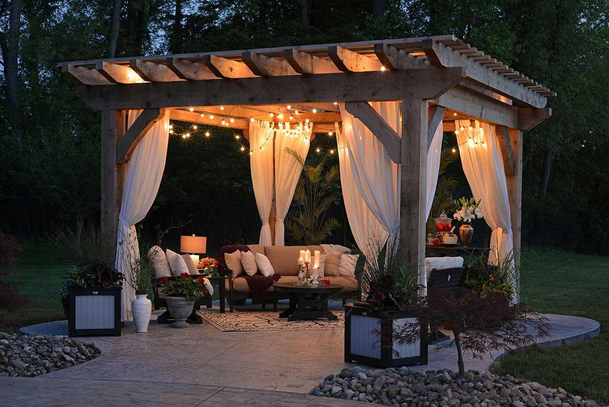 Terass med pergola som är inredd med vita gardiner och ljus i taket