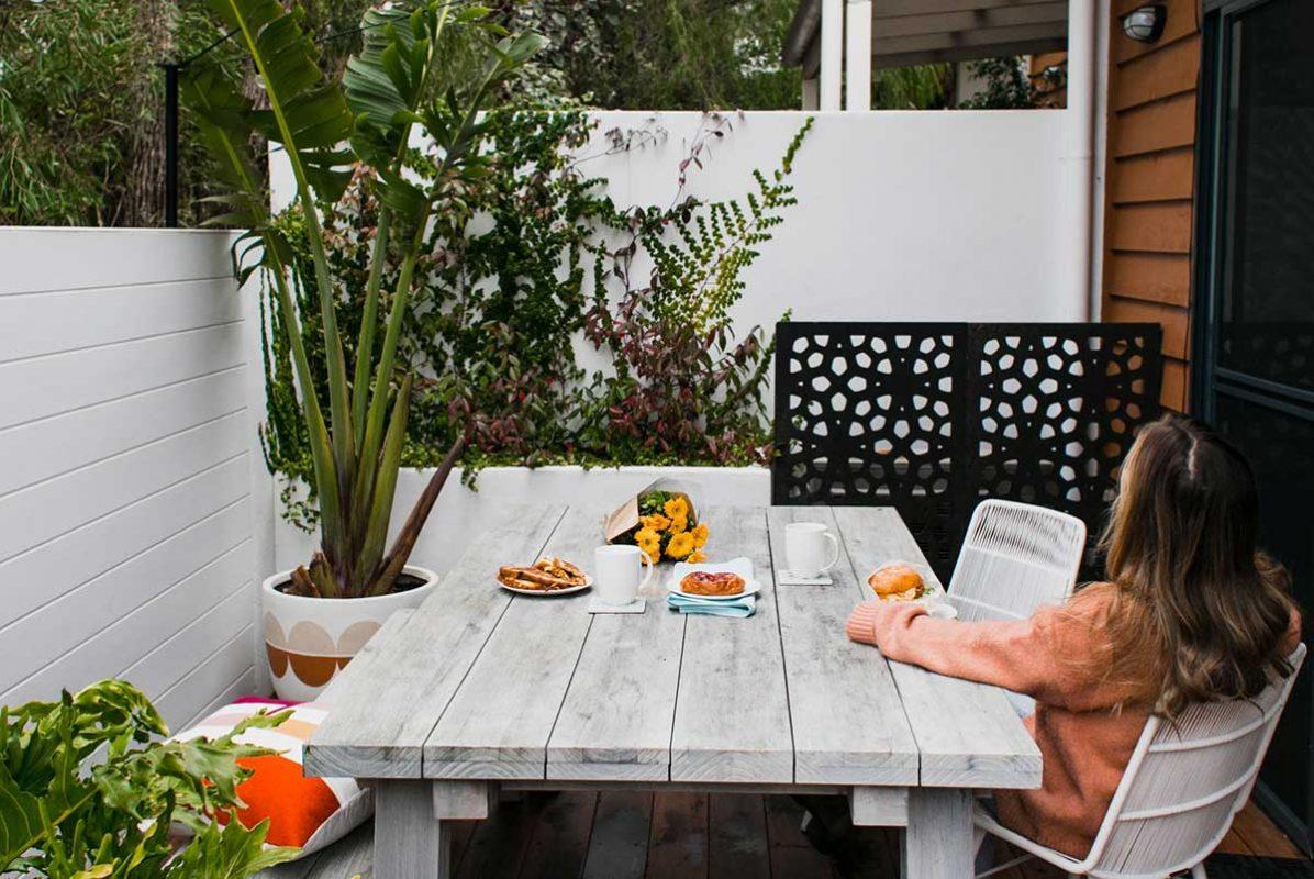 Vitt bord på terassen med kvinna som tittar ut på sin fina växt