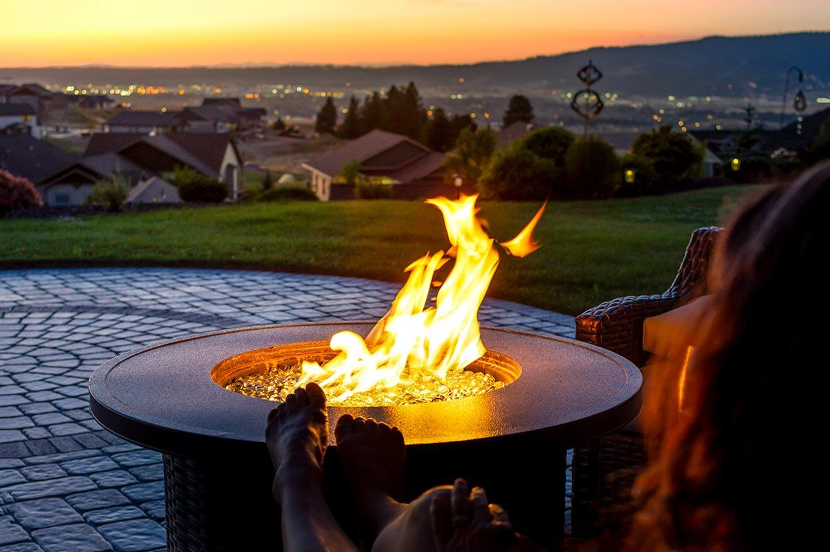 Rund eldstad brinner på uteplats under kvällstid med hus i bakgrunden